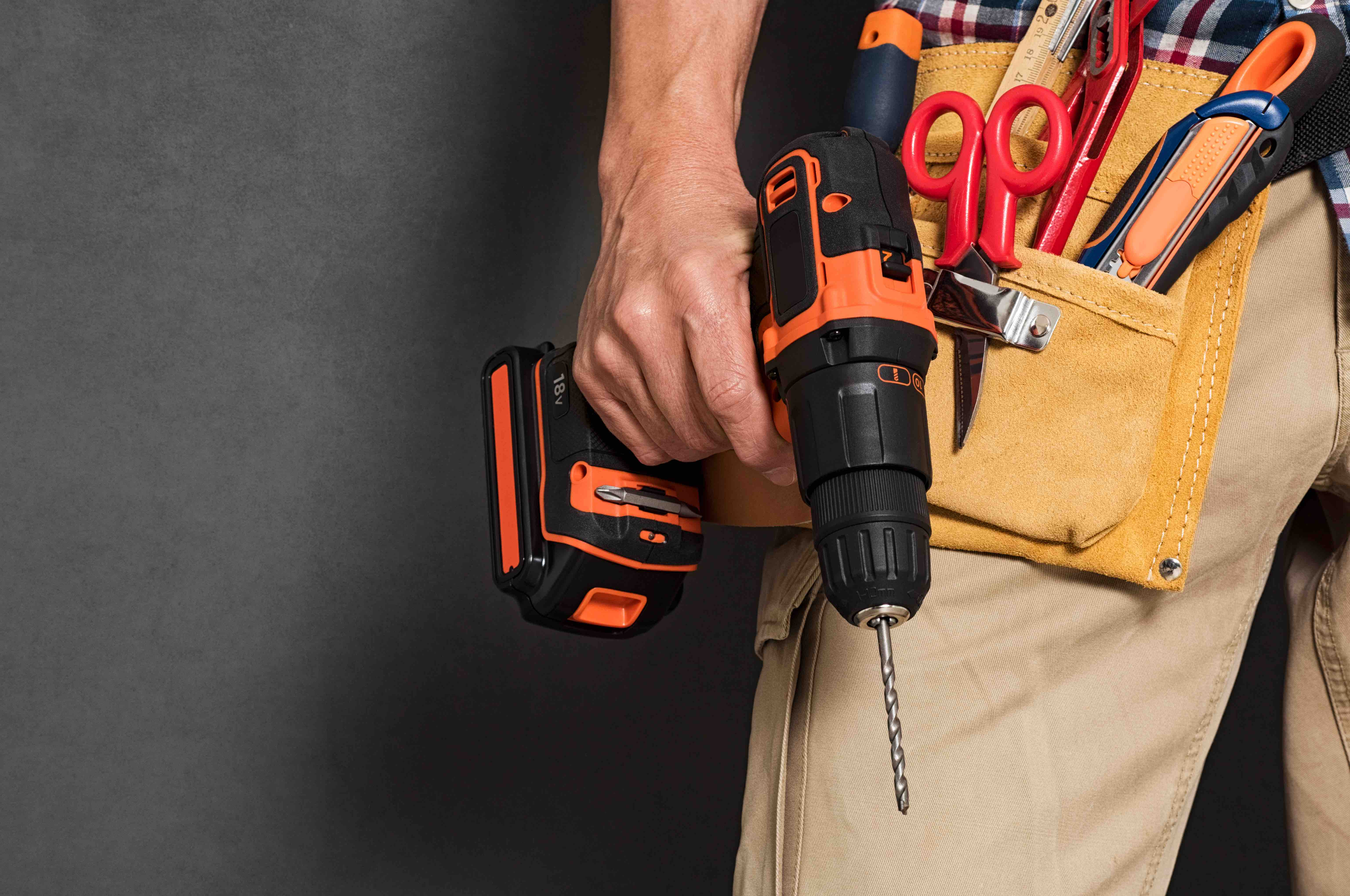 handyman contractor with tool belt holding electric drill for construction